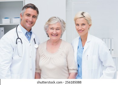 Portrait of doctors and senior patient smiling in clinic
