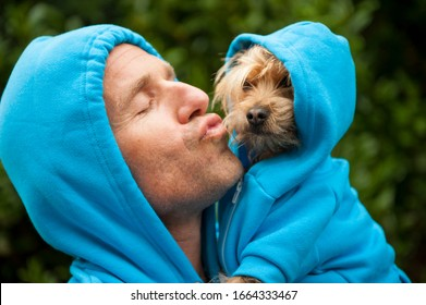 Portrait of dog owner kissing a furry friend in matching blue hoodies outdoors in bright green park background