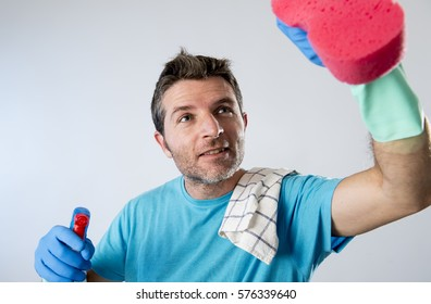 portrait of domestic service man or busy husband smiling happy doing house cleaning with spray bottle and sponge washing glass pointing the camera  isolated even background