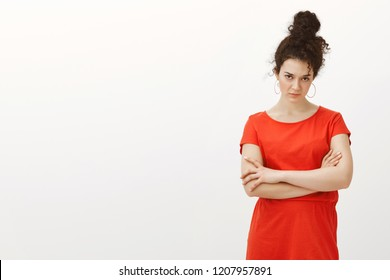 Portrait of doubtful attractive urban female with curly hair combed in bun, holding hands crossed on chest, looking from under forehead with disbelief and serious expression over gray background