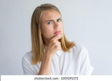 Portrait of doubtful young Caucasian businesswoman wearing white shirt analyzing some idea. Uncertainty and skeptic concept