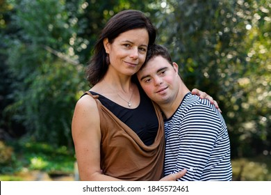Portrait of down syndrome adult man with mother standing outdoors in garden.