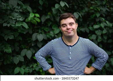 Portrait of down syndrome adult man standing outdoors at green background, looking at camera.