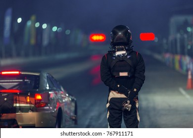 Portrait of a dragster driver with drag car in race track at night.