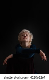 portrait of dreaming beautiful blond woman on black background -  copy space