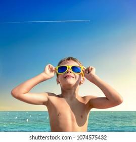 Portrait of dreamy boy in yellow sunglasses on Lloret de Mar beach. Costa Brava, Spain