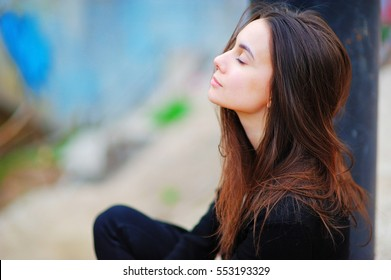 Portrait of a dreamy cute happy woman worker meditating outdoors with big eyes closed, sitting with the effect of blur closeup. De stress relief fit exercise, easy train enjoy career rest time concept