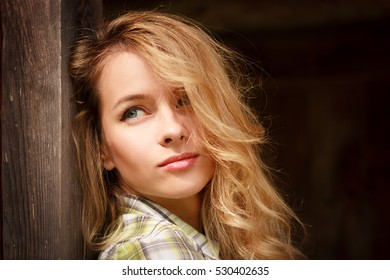 Portrait of a Dreamy Hipster Girl on Wooden Background. Romantic Woman Outdoors. Toned Photo with Copy Space.