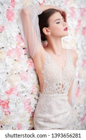 A portrait of a dreamy lady in a wedding dress posing indoor with flowers. Wedding, beauty, fashion.