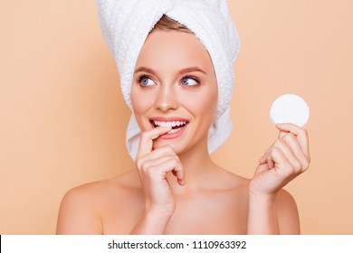 Portrait of dreamy minded ponder girl with turban on head holding using white cotton pad for removing makeup isolated on beige background