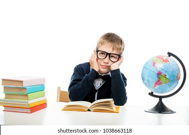 portrait of a dreamy schoolboy at a table with books and a globe isolated