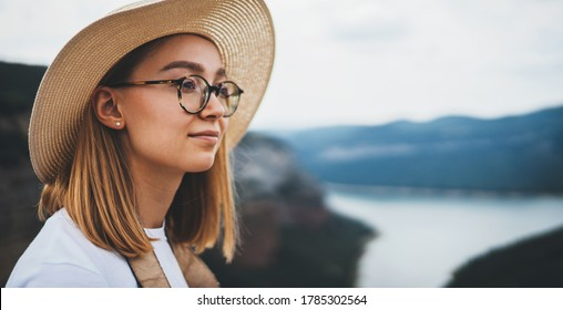 portrait of dreamy young blonde in straw summer hat and fashion glasses background of natural mountain landscape and blue sky, empty space for your design