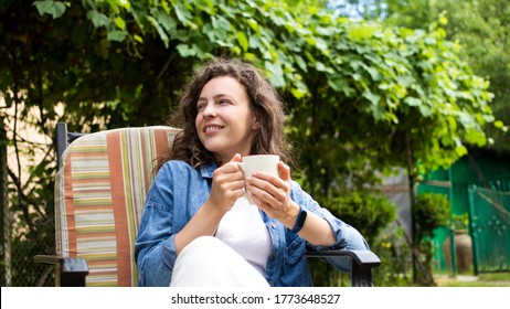 Portrait of dreamy young woman enjoying drinking coffee in the morning sitting on chair on home terrace on green garden background.Happy morning routine,day planning,enjoying life,to be in the moment