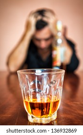 Portrait of a drunk and depressed man addicted to alcohol (Focused on the drink, his face is out of focus)