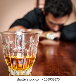 Portrait of a drunk  man addicted to alcohol sleeping with his head on the table  (Focused on the drink, his face is out of focus)