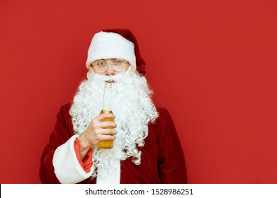 Portrait of drunk Santa Claus with bottle of beer in hands on red background, looks into camera. Santa in alcoholic span isolated on red background. Drunk man santa for new year.