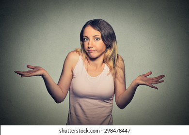 Portrait dumb looking woman arms out shrugs shoulders who cares so what I don't know isolated on gray wall background. Negative human emotion, facial expression body language life perception attitude