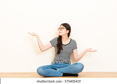 Portrait dumb looking woman arms out shrugs shoulders isolated on white blank background. Negative human emotion, facial expression body language life perception attitude sitting on wooden floor.