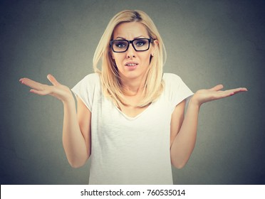 Portrait dumb looking woman arms out shrugs shoulders I don't know isolated on gray background. Negative emotion body language