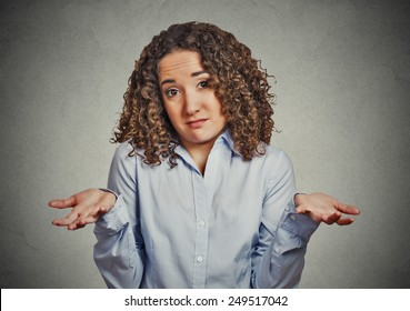 Portrait dumb young woman arms out shrugs shoulders who cares so what I don't know isolated grey wall background. Negative human emotion, facial expression body language life perception attitude