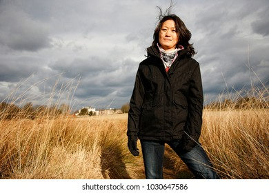 Portrait East Asian Woman Looking at Camera Standing in Dried Reed Fields, Dramatic Cloudy Sky Present