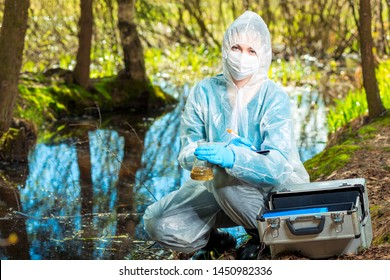 portrait of an ecologist in protective clothing while working, taking water samples from a forest river for analysis