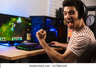 Portrait of ecstatic gamer guy in headphones screaming and rejoicing while playing video games on computer