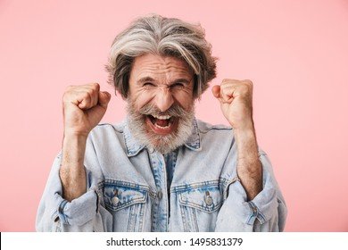 Portrait of ecstatic old man with gray beard laughing and clenching fists like winner isolated over pink background