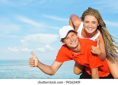 Portrait of ecstatic young couple against sea.