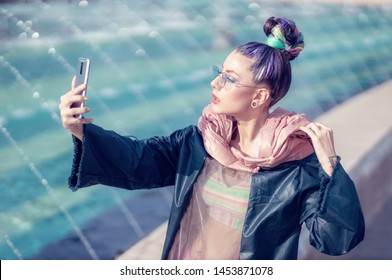 Portrait of edgy girl with crazy look taking self-portraits (selfie). Urban outdoor with fountains in background. Model girl wearing stylish sunglasses, avant-garde hairstyle and make-up.