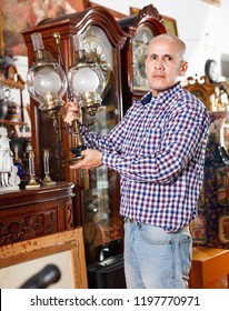 Portrait of efficient  successful owner of antiques shop among vintage things