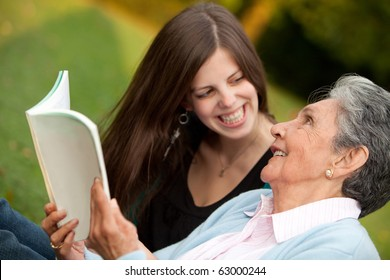 Portrait of an elder mother and granddaughter reading a book outdoors