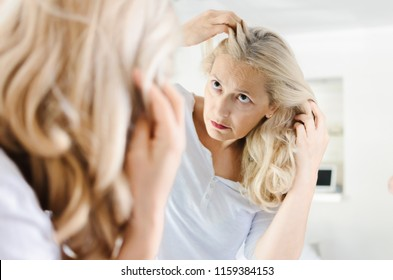 Portrait of elder woman checking her hair in front of a mirror at home.