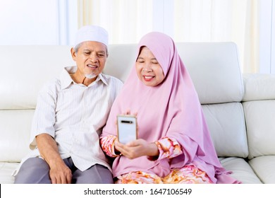 Portrait of elderly Asian muslim couple holding a phone, while video calling their grandchildren in their living room