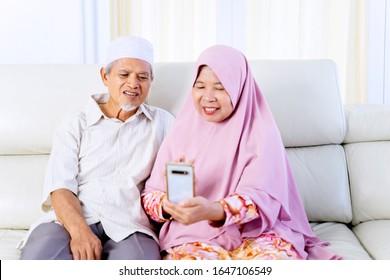 Porträt älterer asiatischer Muslime, die ein Telefon halten, während Video ihre Enkel im Wohnzimmer anrufen