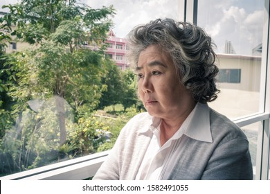 Portrait of elderly Asian senior woman with grey hair looking out window and sad emotion, close up lifestyle concept