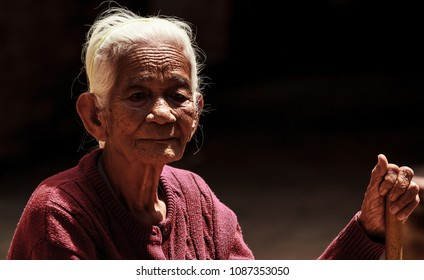 Portrait of an elderly Asian wrinkled woman holding walking cane on black background. Family Relation, Health Care, Help, Support, Insurance, Gratuity, Social Responsibility and Aging Society concept