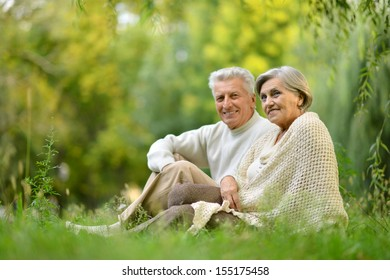 Portrait of a elderly couple sitting in autumn park