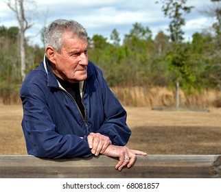 Portrait Of An Elderly Gentleman Leaning On Fence Railing