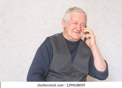 Portrait of elderly happy business man of eighty years talks by phone about business