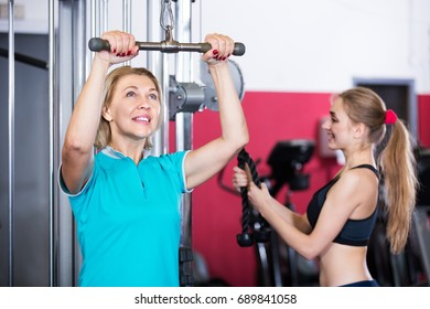 Portrait of elderly and happy young women doing powerlifting on machines in jym