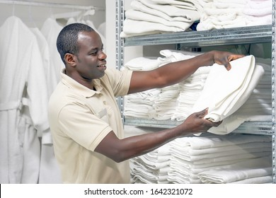 Portrait of elderly hotel worker african man lays a clean white towel on the shelves. Hotel african staff workers. Hotel linen cleaning services.