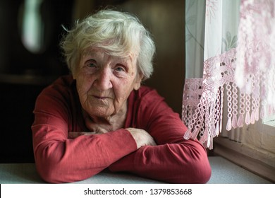 Portrait of elderly lady is sitting at the kitchen table.