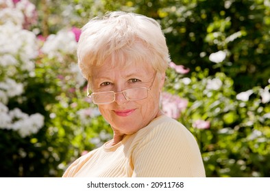 Portrait of the elderly laughing woman in glasses