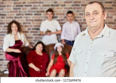 Portrait of elderly man against family sitting on sofa in room.
