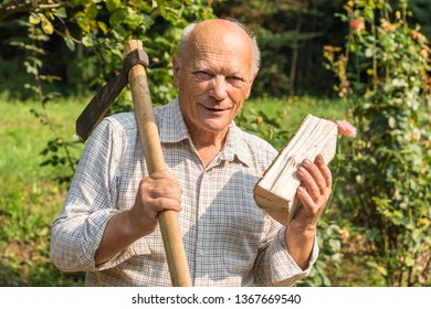 Portrait of elderly man with ax on his shoulder and a half of wood in his hand in the garden.