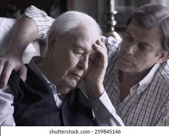 Portrait of an elderly man, comforted by his son