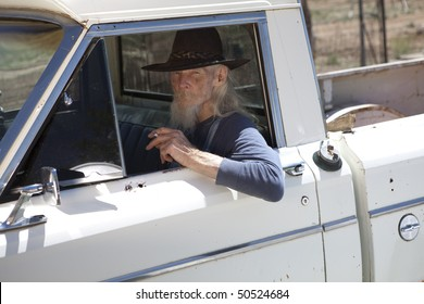 Portrait of an elderly man with a cowboy hat and white beard, driving a pickup truck and staring out the window. He is holding a cigarette and looking at the camera. Horizontal format.