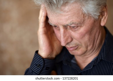 portrait of an elderly man with a headache on a beige background