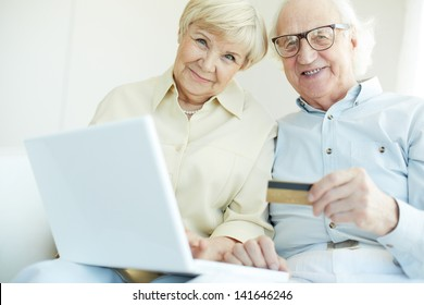 Portrait of elderly man and his wife with latop and plastic card looking at camera